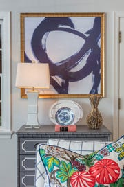 The large modern painting is lovely balanced with the traditional chest of drawers, with its bamboo trim.