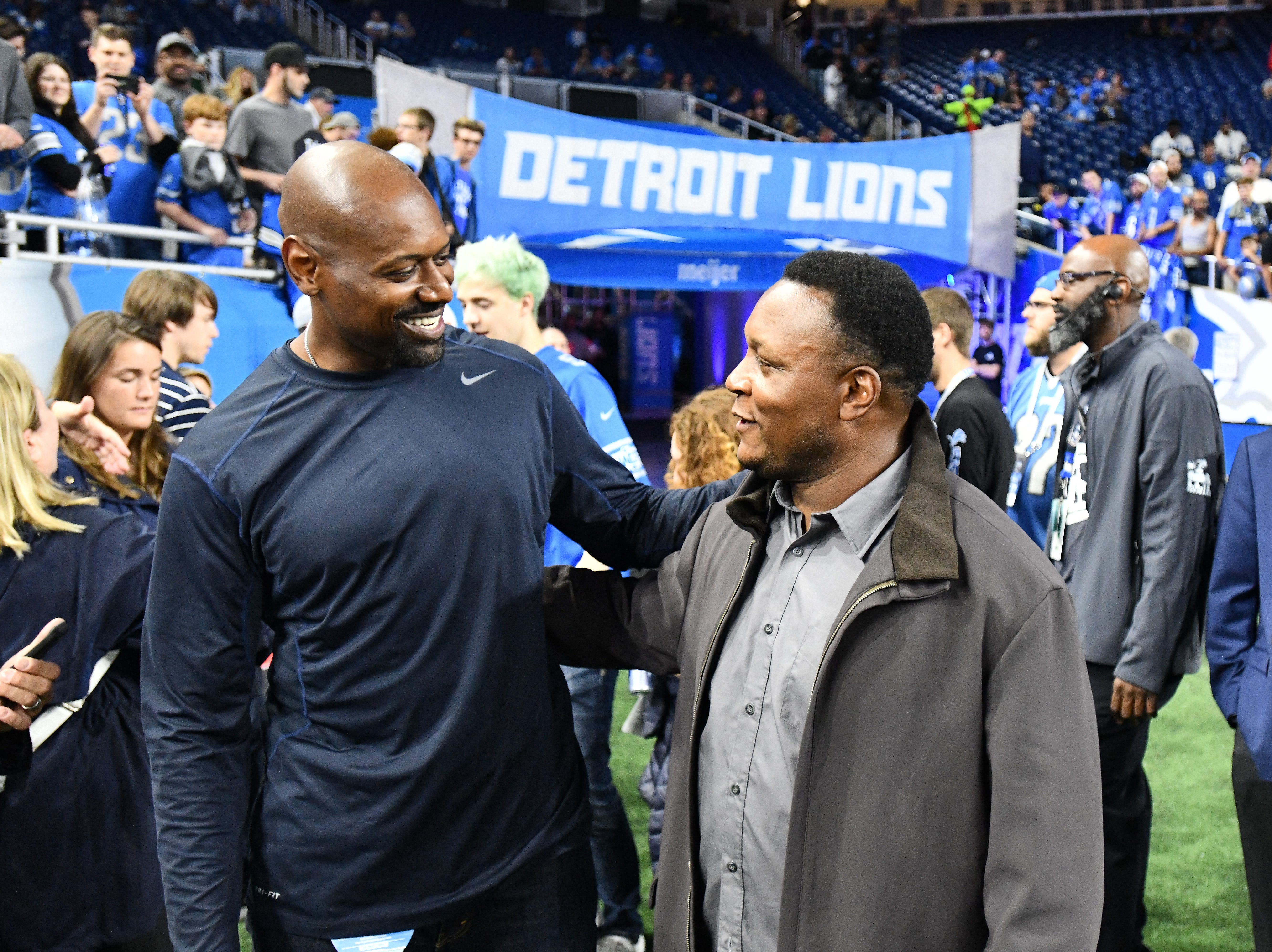 Former Lions Herman Moore and Barry Sanders chat on the field before the game.