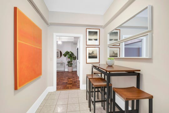 A pop of orange in the form of artwork helps add color to this kitchen nook.