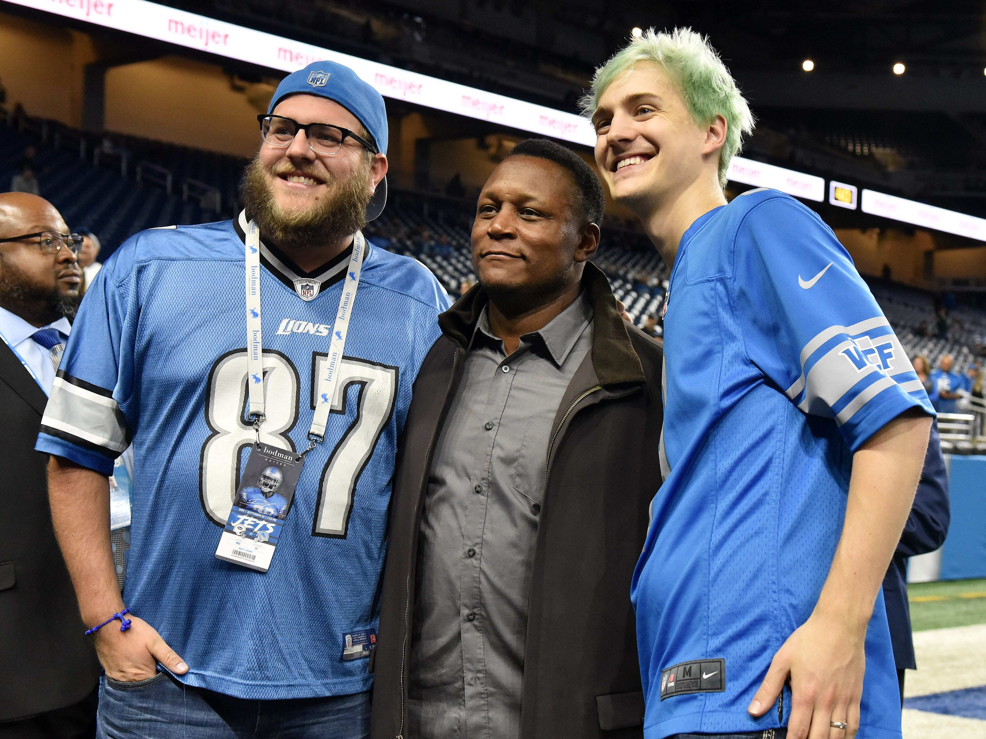 "Tyler ""Ninja"" Blevins, right, with former Lions running back Barry Sanders before the game and Blevins' brother, Jonathan Blevins, left."