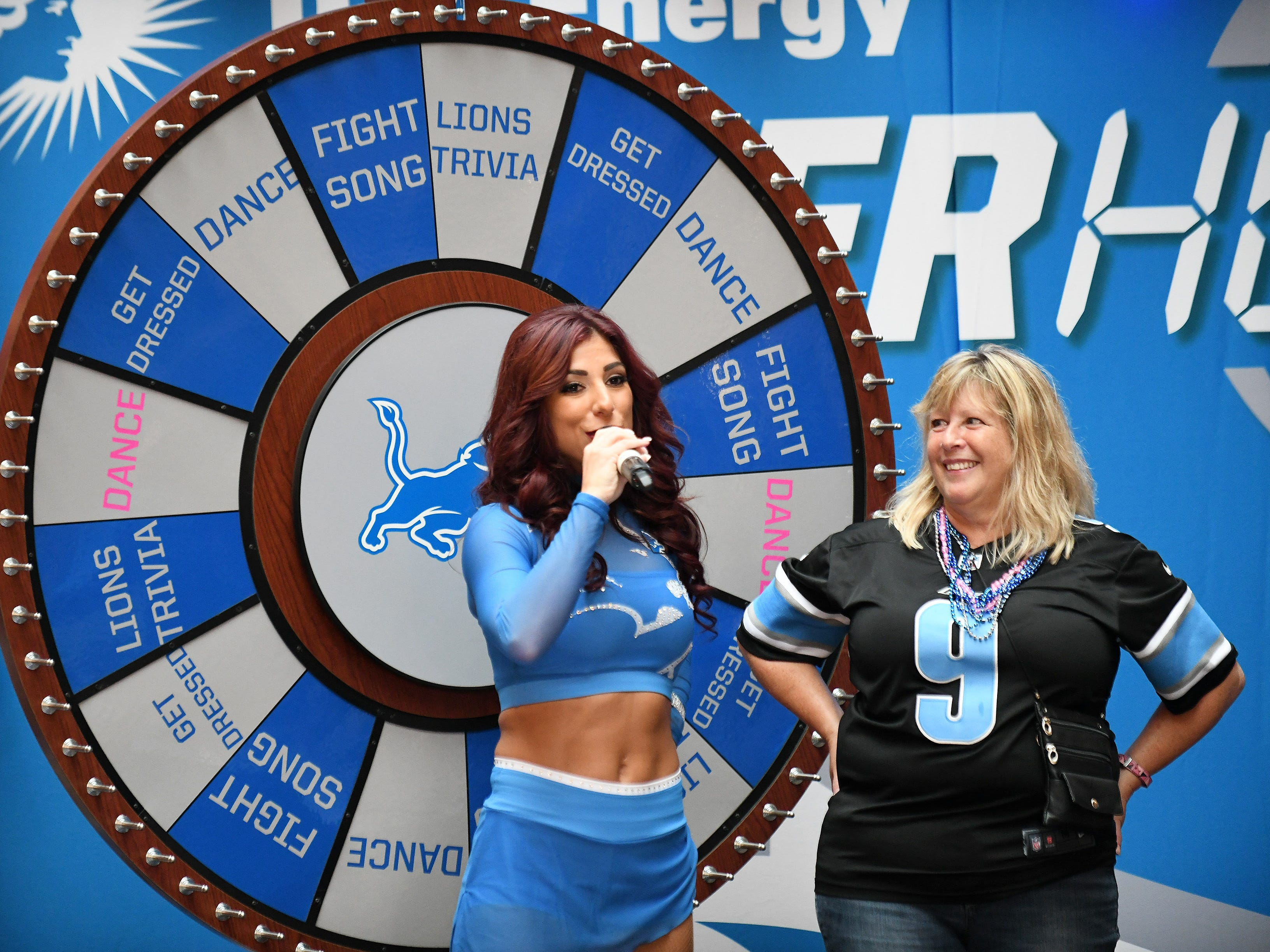 Mary Mullin of Waterford, right, waits to see if her answer to a Lions trivia question is correct at fan activities with the Lions cheerleaders.