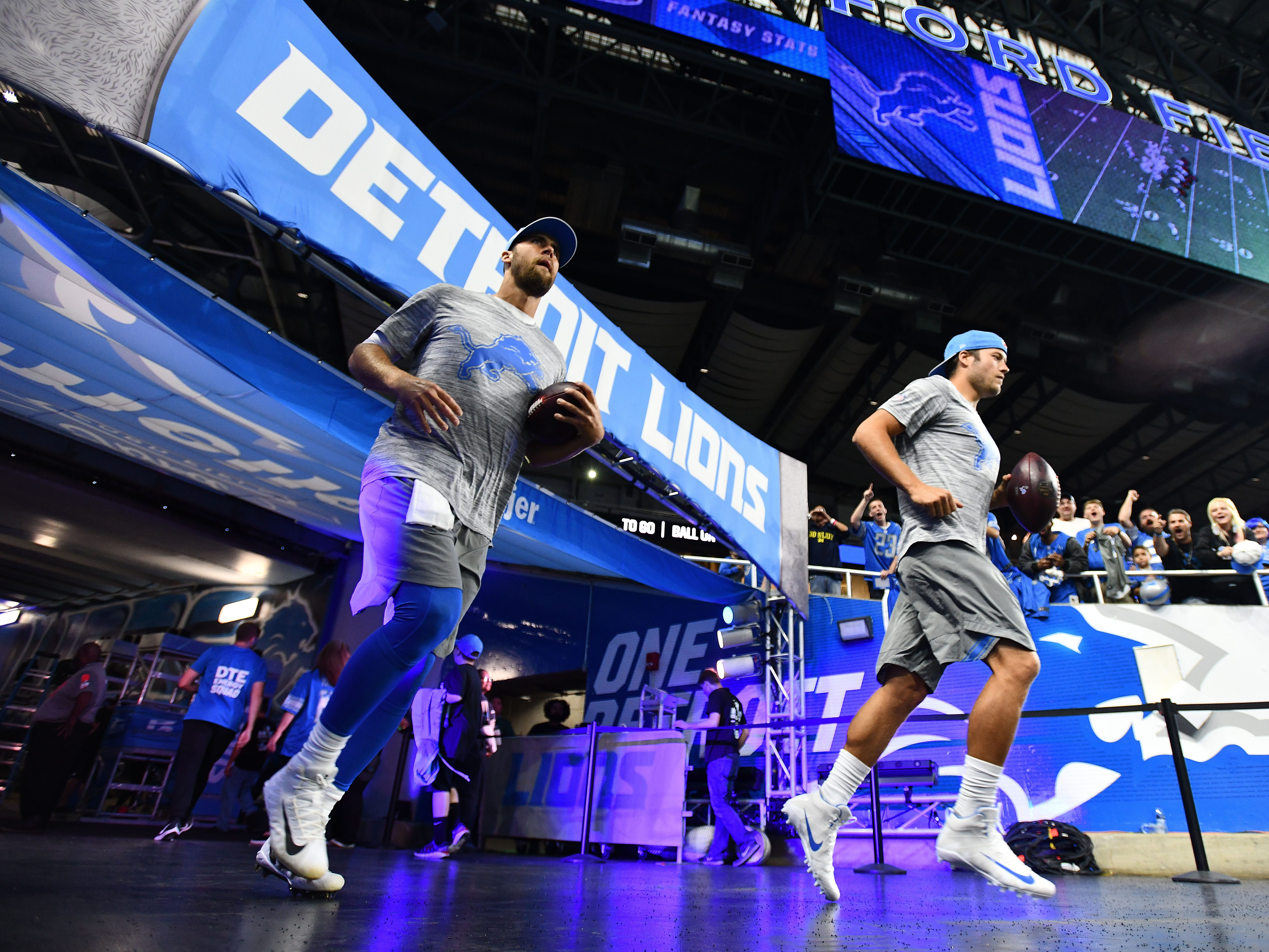 Lions quarterbacks Matt Cassel and Matthew Stafford make their way onto the field for warmups before the Detroit Lions take on the New York Jets at Ford Field in Detroit, Michigan on September 10, 2018.