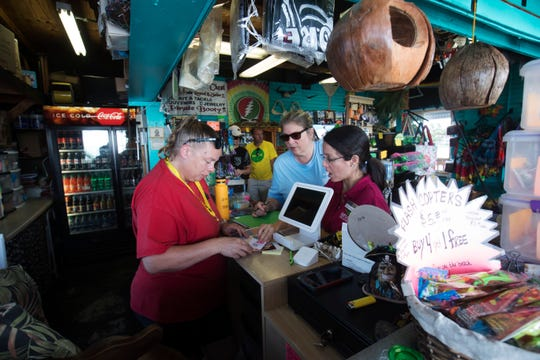 Megan Contreras and Francesca Donlan from the Lee County Visitors and Convention Bureau hand out literature to Rudy's Treasure Chest employee Stacie Hall earlier this month. Hall works at the Fort Myers Beach pier business. Employees of Lee County are blanketing businesses on Fort Myers Beach and Sanibel affected by the red tide outbreak. They are offering a new program called One Lee in hopes of attracting Lee County locals to stay, shop and dine in the coastal communities.