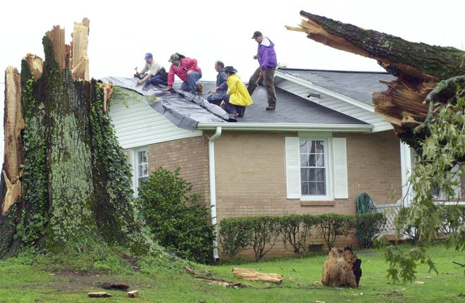 Men work to put down plastic on the roof of a home damaged by a tornado from the remnants of Hurricane Ivan, Sept. 17, 2004, in Westminster.