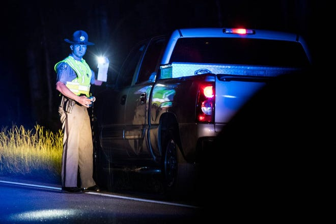 A South Carolina Trooper holds an empty can of beer during a traffic stop that resulted in a high speed chase on Friday night, Aug. 17, 2018, near Camden, S.C.