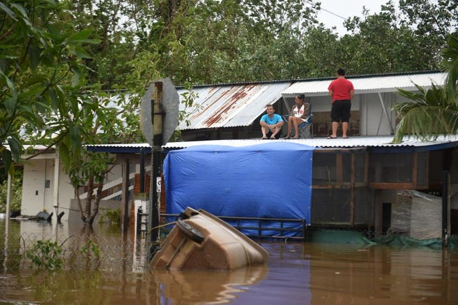 A Yigo family stays above flooded waters on their roof in the East Gayinero area of Yigo, in the aftermath of Typhoon Mangkhut on Sept. 11.