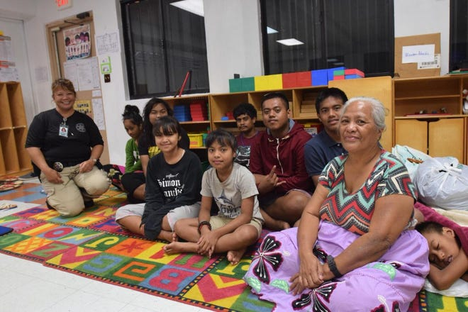 Yigo resident Elly Peter sits with some of her grandchildren, neighbor and school staff at a Machananao Elementary School shelter on Sept. 10, 2018.