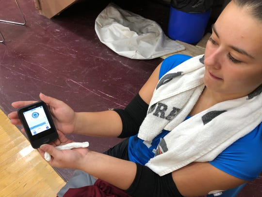Henderson County senior volleyball player Maggie Vincent shows off the monitor that displays her blood sugar levels. The monitor is connected via bluetooth to a continuous glucose monitor that she wears.