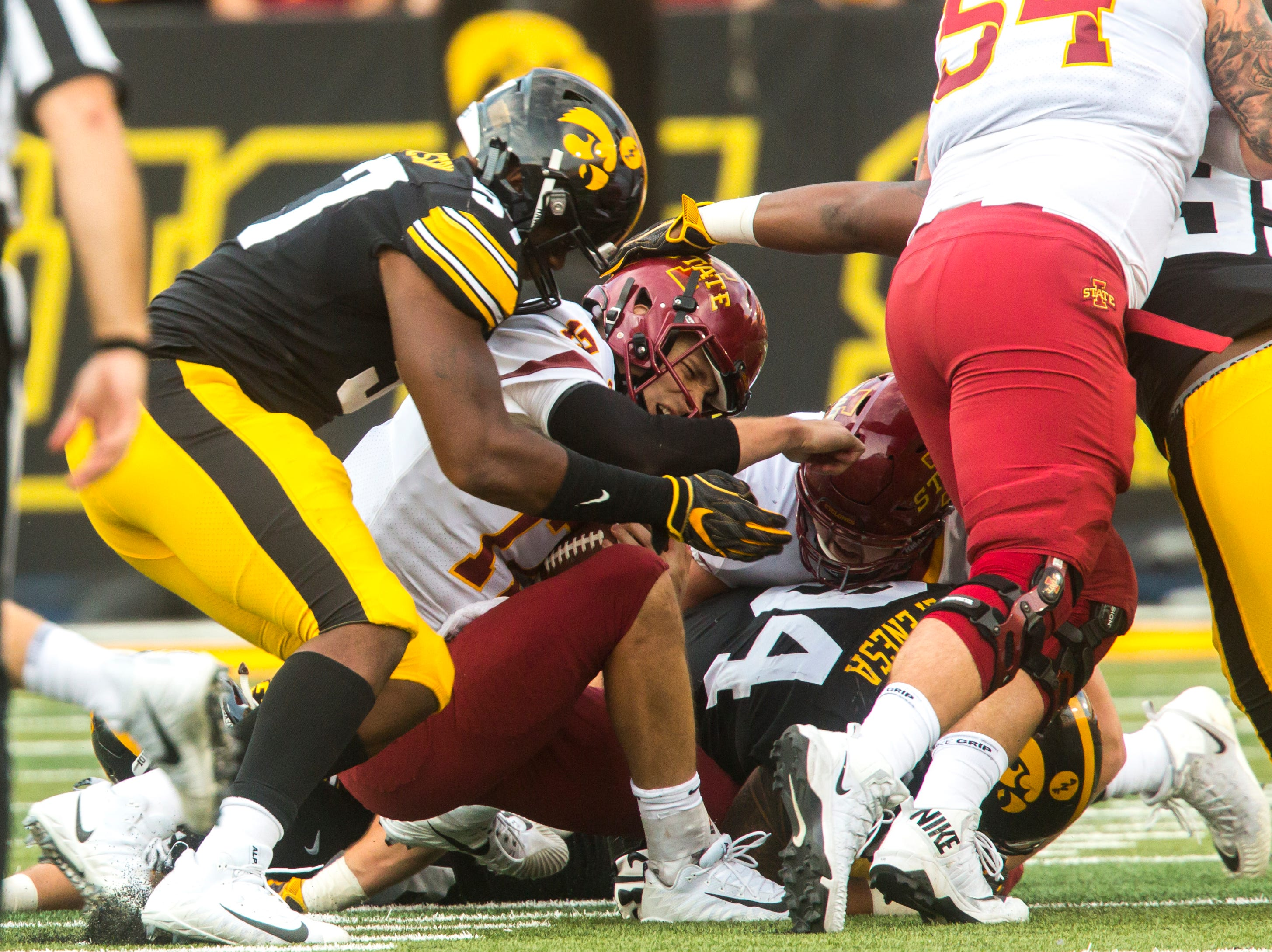 Iowa State quarterback Kyle Kempt (17) gets sacked by Iowa defensive end Chauncey Golston (57) and defensive end A.J. Epenesa (94) during the Cy-Hawk NCAA football game on Saturday, Sept. 8, 2018, at Kinnick Stadium in Iowa City.