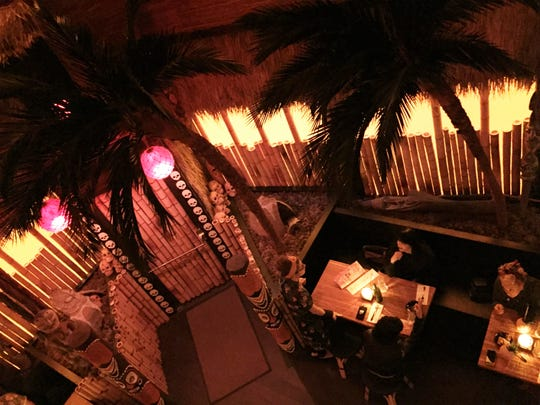Palm trees, bamboo walls, totems and late sunset light at The Inferno Room in the Fountain Square area of Indianapolis.