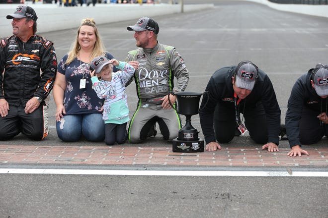 Lilly Diabetes 250 winner Justiin Allgaier celebrates with his wife Ashley, their daughter Harper Grace and member of his crew on the yard of bricks at Indianapolis Motor Speedway on Monday, Sept.10, 2018.