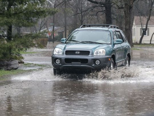 A car drives through the flooded intersection of Caroline and 67th streets in Indianapolis in April 2018. A range of 4-6 inches of rain fell in the Indianapolis area this weekend, causing some flooding of streets.