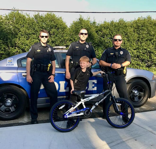 The boy whose bike was stolen shows off his new one with the officers who purchased it for him.