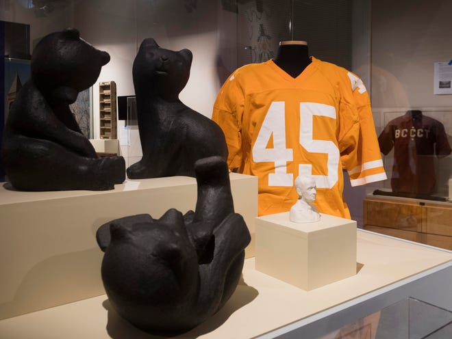 """Bears created by East Tennessee potter Doug Ferguson sit in front of a signed Johnny Majors University of Tennessee football jersey. The bears and jersey are part of a new exhibit at the Museum of East Tennessee History that showcases items the museum has acquired in its 25 years. That exhibit is called """"A Home for Our Past: The Museum of East Tennessee History at 25."""""""