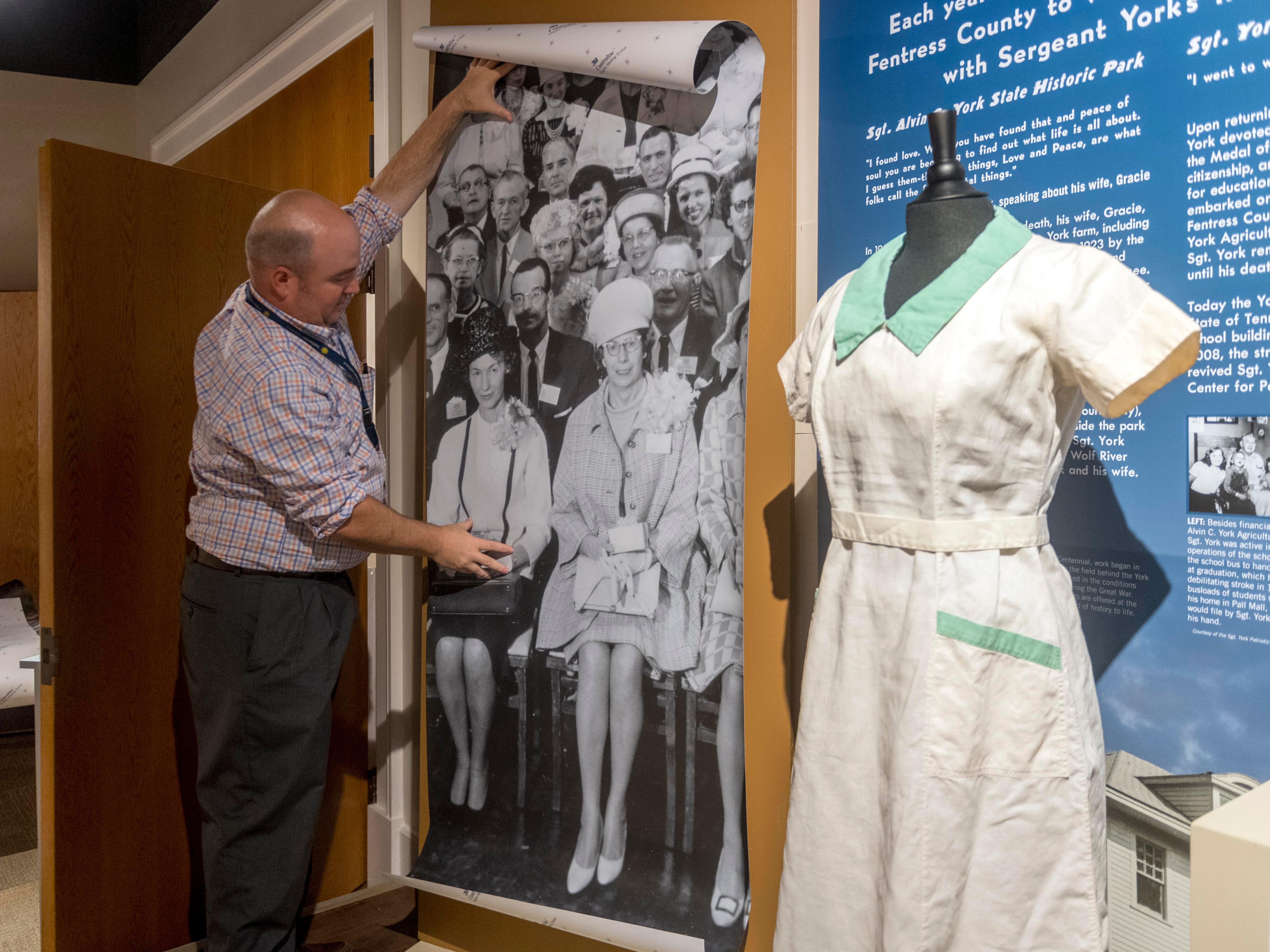 "Adam Alfrey of the Museum of East Tennessee History works on setting up the exhibit, ""A House for Our Past: The Museum of East Tennessee History at 25."" In the photograph being hung is a picture of Ethel Byerley, left, who wore the displayed green and white Standard Knitting Mill uniform."