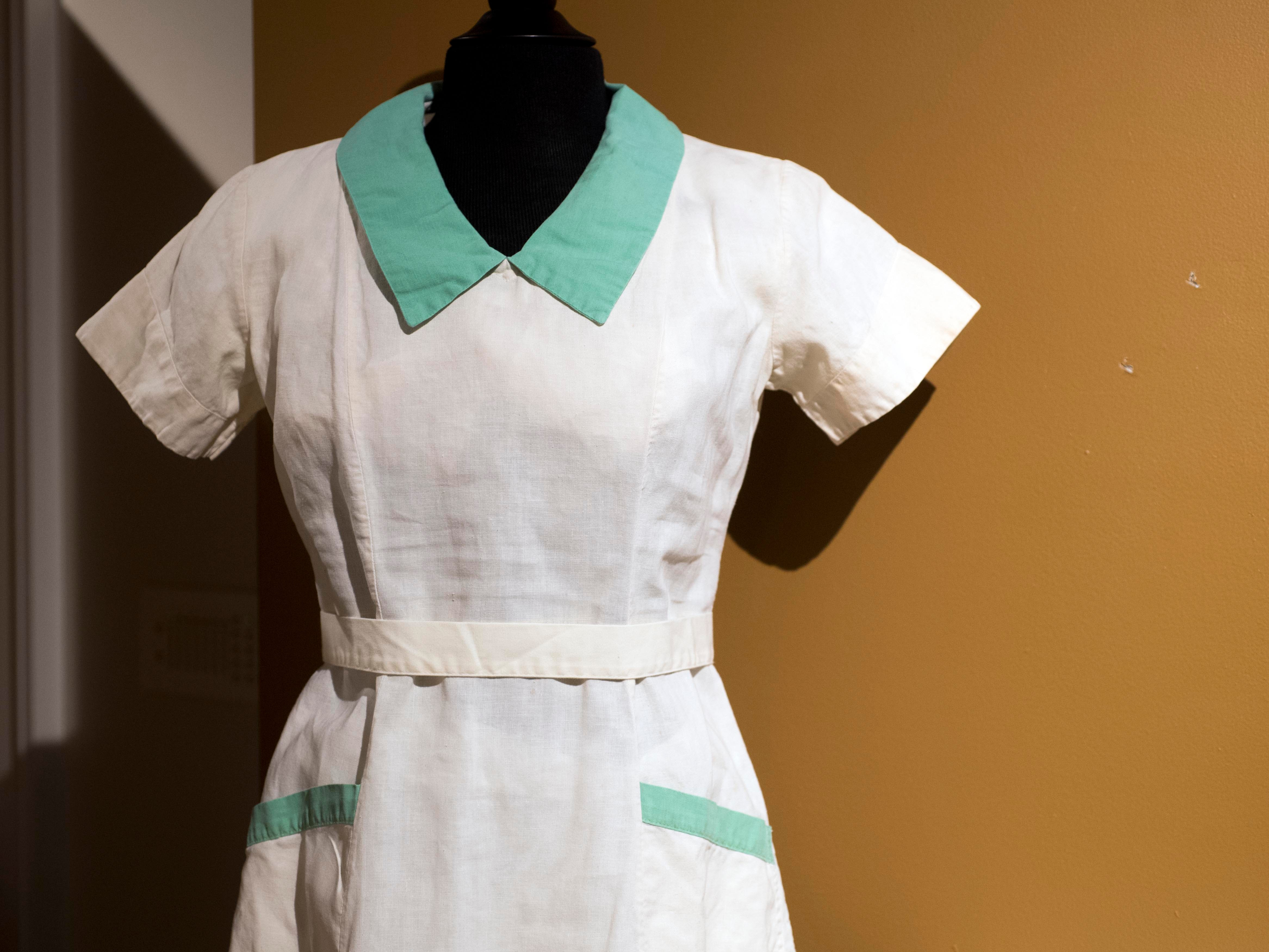 This white with green trim uniform was worn by Ethel Byerley when she worked as a supervisor at Standard Knitting Mill. The mill was founded in 1900 with 50 employees and grew to more than 4,000 three decades later. Byerley supervised 40 workers who worn green dresses with white trim. The uniform is from the 1950s-60s.