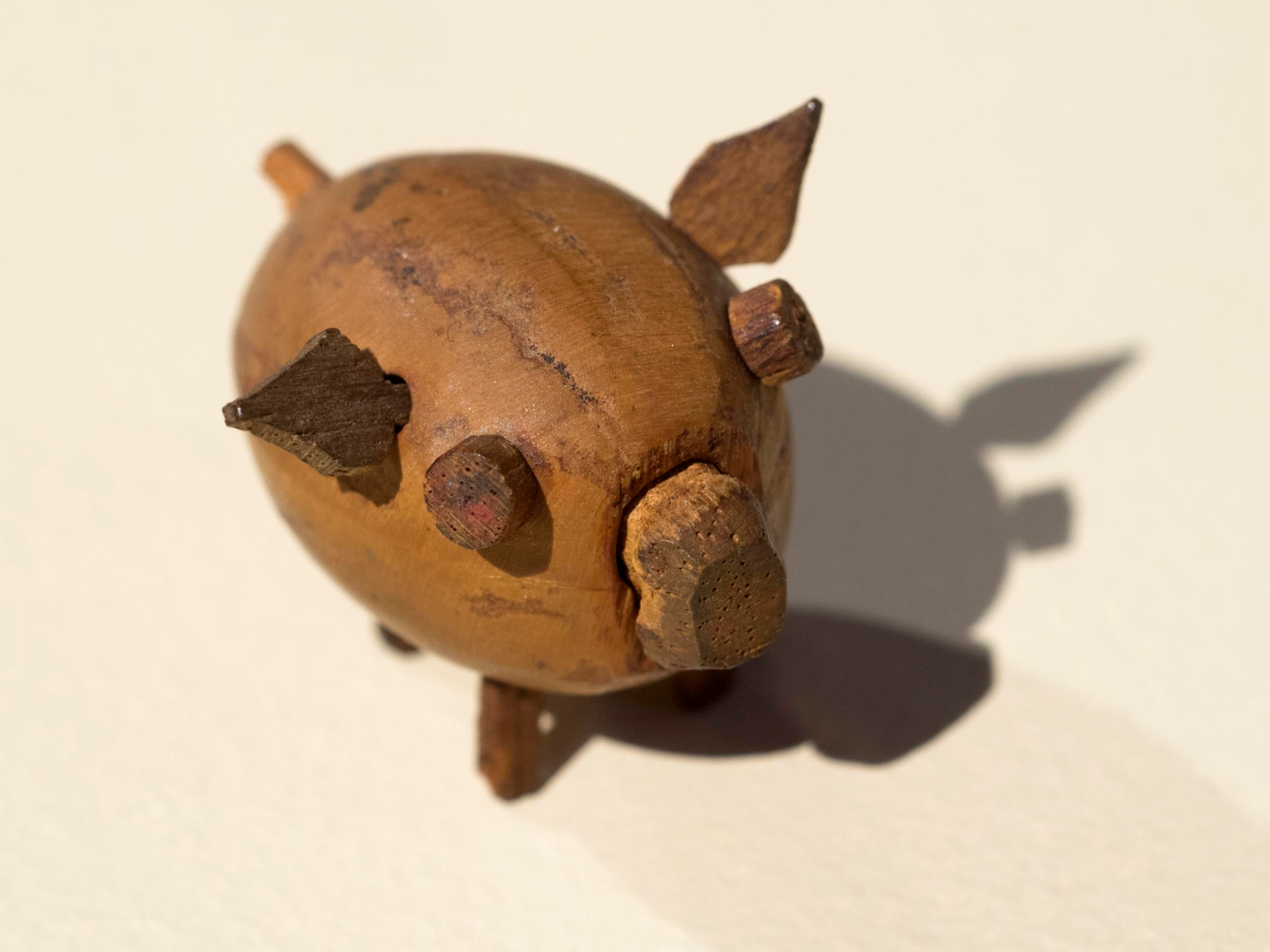 A Brushy Mountain State Penitentiary prisoner hollowed out an acorn to carve this tiny pig with a wooden snout. Prisoner-made items were sold in neighboring towns to make cigarette money. This pig cost 50 cents. It was a toy. Remove the wooden snout, capture a fly, replace the snout. So long as the fly buzzed around, the pig's tiny ears wiggled.