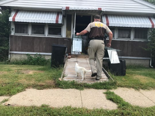 Animal Control Officer Seth Kirkendall sets up traps for the indoor and outdoor cats left behind in Clarks Hill.