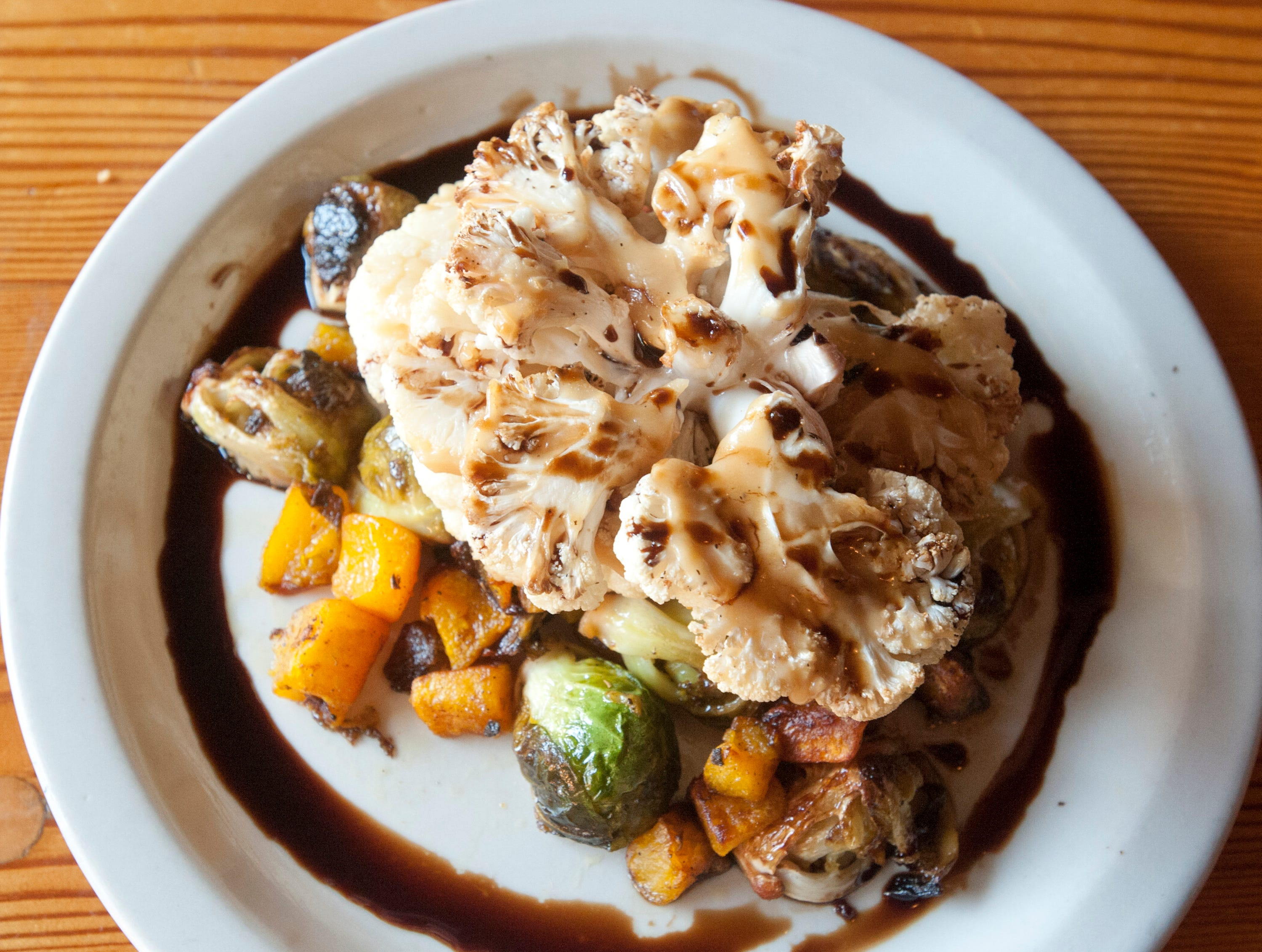 The Silver Dollar Bar and Restaurant's cauliflower steak is accompanied by roasted Brussel sprouts, butternut squash, sage butter, and a15-year-old aged balsamic sauce.