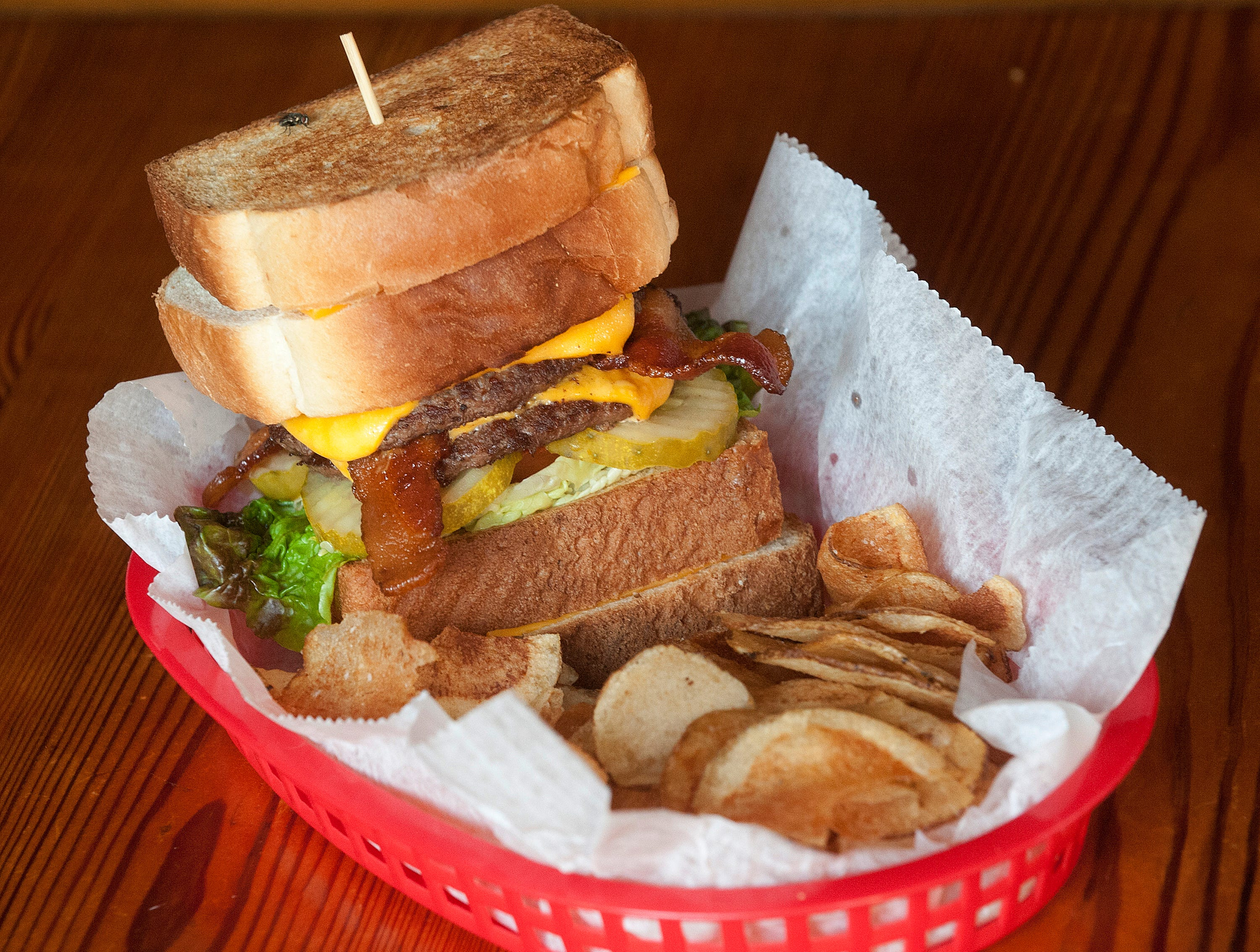 The Silver Dollar Bar and Restaurant's ultimate burger is topped with bacon, lettuce and tomato, pickles, American cheese, and served between two grilled cheese sandwiches. The dish is often accompanied by an order of French fries or home-made potato chips (seen here.)