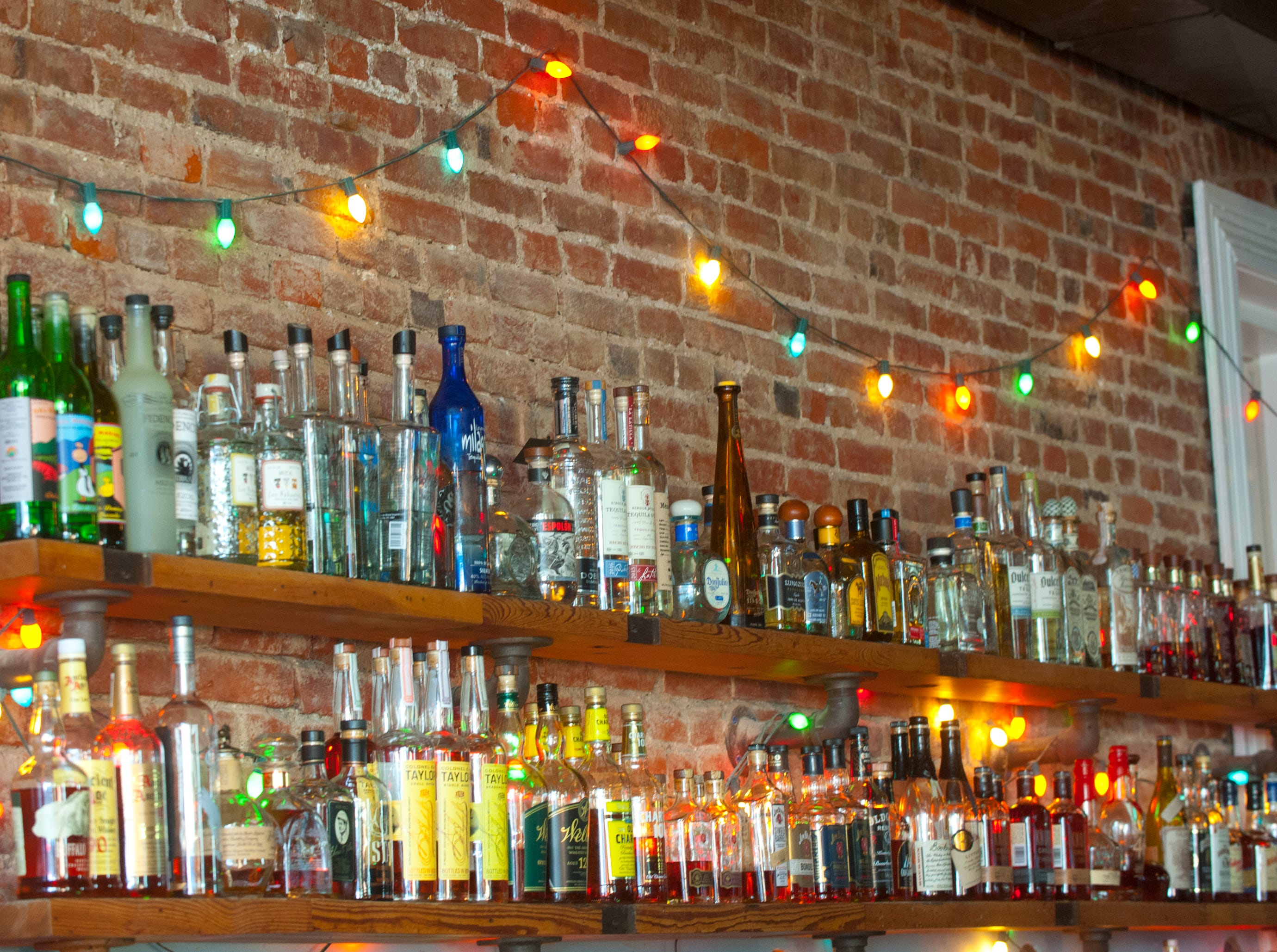 Bottles of liquor stack along the wall of the Silver Dollar Bar and Restaurant's long wood bar.
