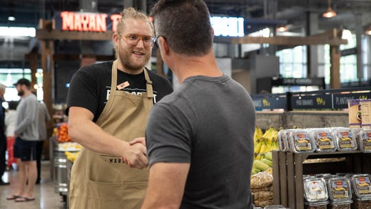 A Bridge Street Market employee greets a customer on the grocery store's opening day.