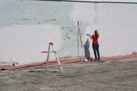 Manitowoc artist Stephanie Carpenter works on a mural.