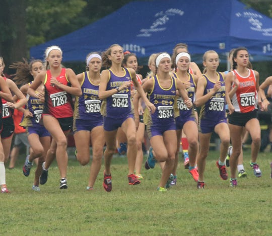 The Lexington girls cross county team run at the starting line of the Tiffin Cross Country Carnival on Saturday.