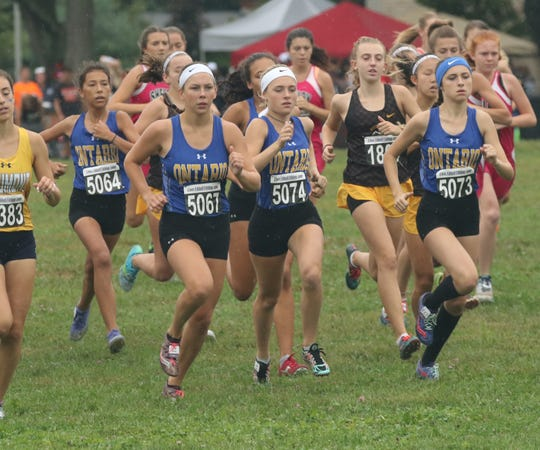 The Ontario girls cross county team run at the starting line of the Tiffin Cross Country Carnival on Saturday.