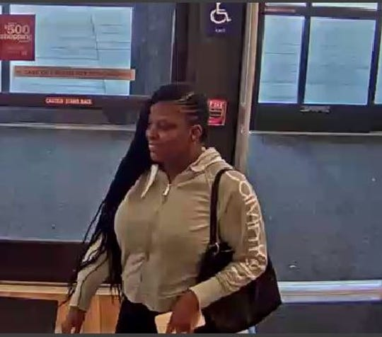 A surveillance photo shows one of the two TJ Maxx theft suspects entering the store carrying a black tote bag.