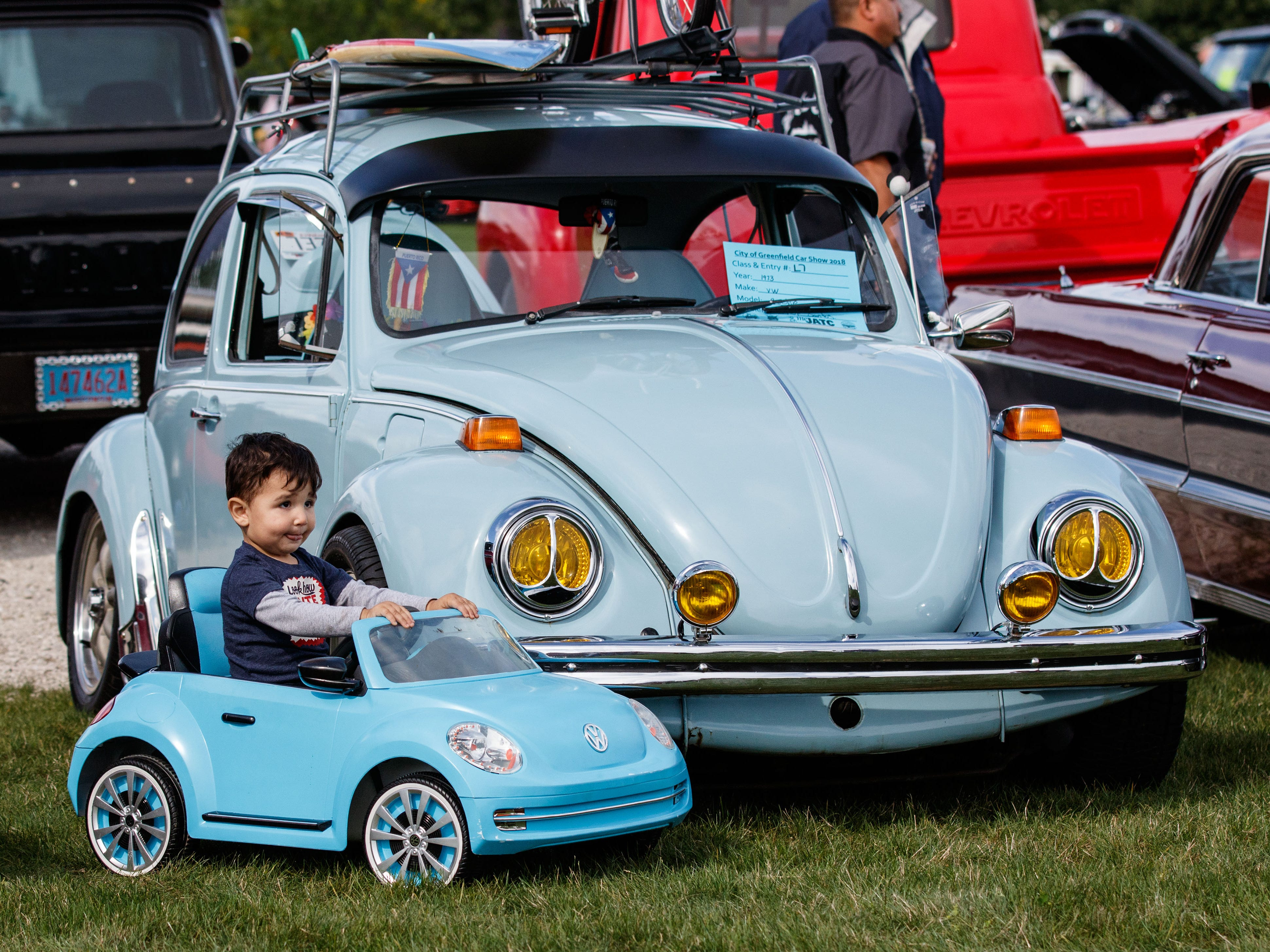 Two-year-old Kristian Santos of Milwaukee shows off his miniature VW alongside his father's original 1973 Beetle during the City of Greenfield's 2nd annual Car Show in Konkel Park on Saturday, Sept. 8, 2018.