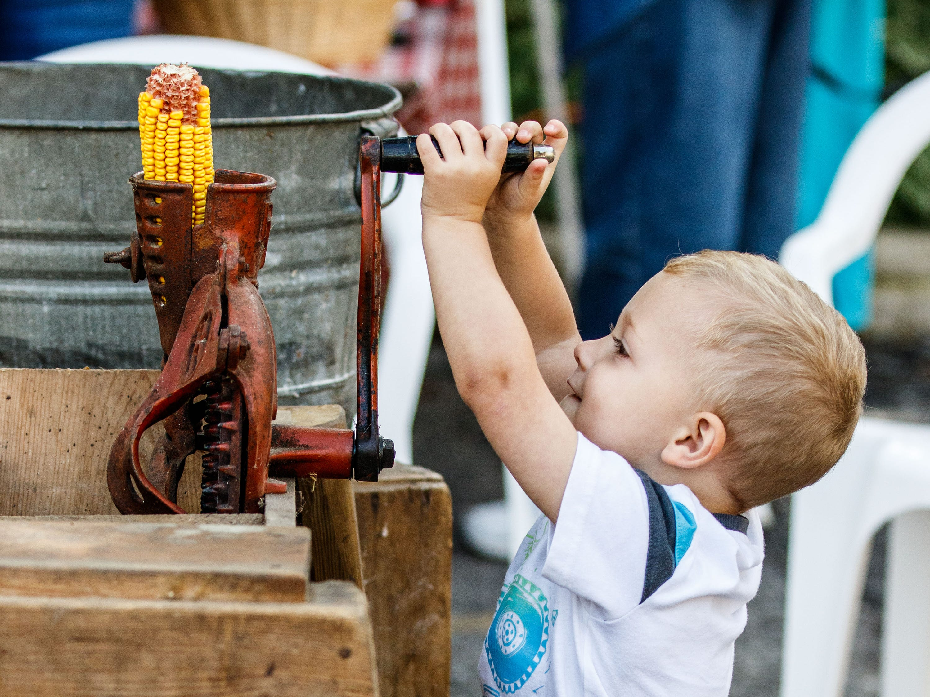 Two-year-old Abe Heard of Pewaukee tries out a hand-cranked corn sheller during Harvest Fest at the Clark House Museum in Pewaukee on Sunday, Sept. 9, 2018. The annual event features hands-on activities and demonstrations of blacksmith, carving, butter churning, corn shelling, square dancing and more.