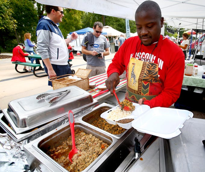 William Kazibwe of Immy's African Cuisine prepares a plate for a customer during the sixth annual Taste of Mequon in the vicinity of City Hall and on Cedarburg Road on Sept. 8.