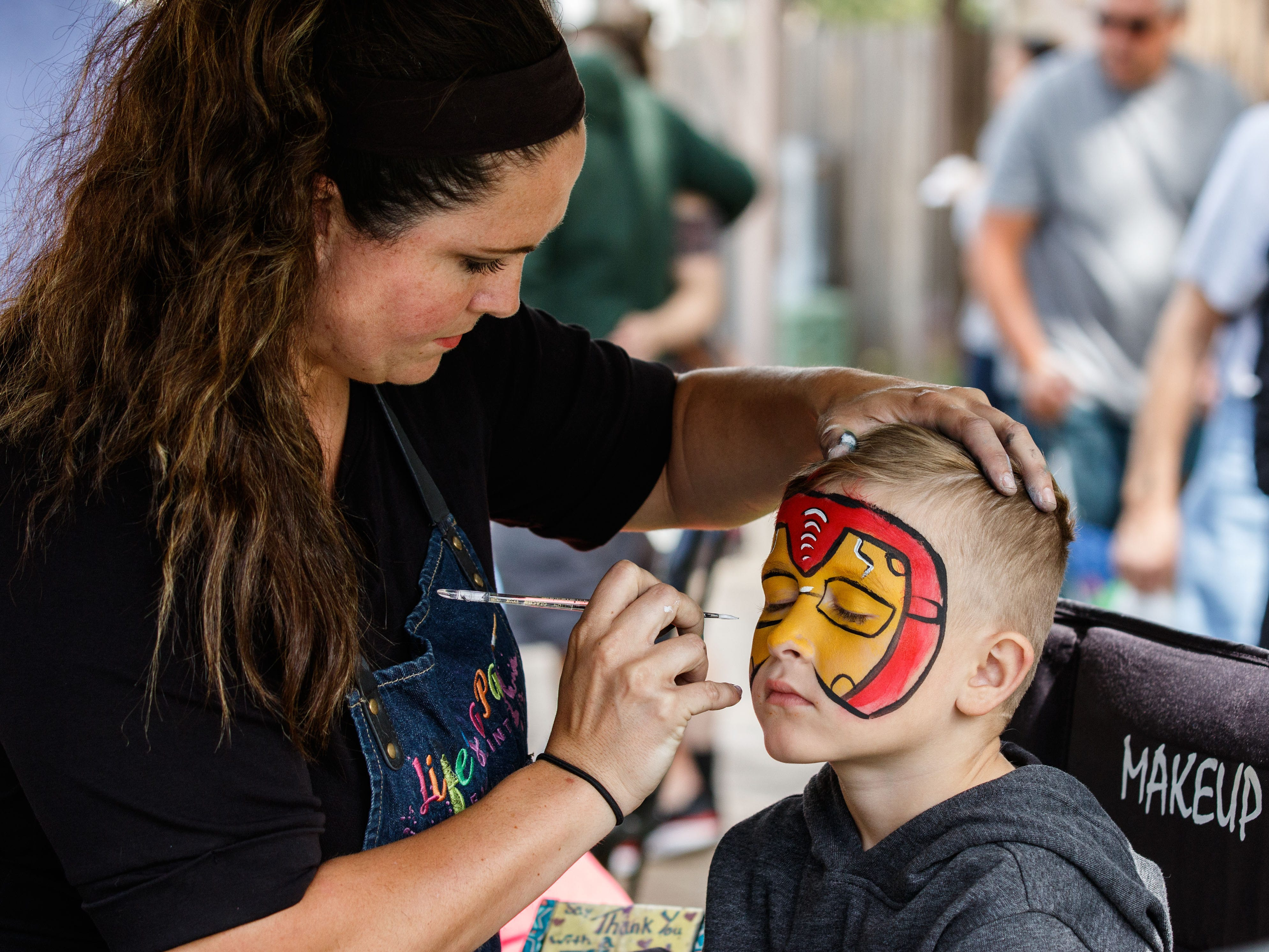 Five-year-old Gibson Bryant of Oconomowoc sits for a face painting by Leea Woolard of Life's A Party Face Painting during the 7th annual Fall Festival hosted by the Downtown Oconomowoc Business Association on Saturday, Sept. 8, 2018. The event features live music, dancing, shopping, arts and crafts, food, refreshments and more.