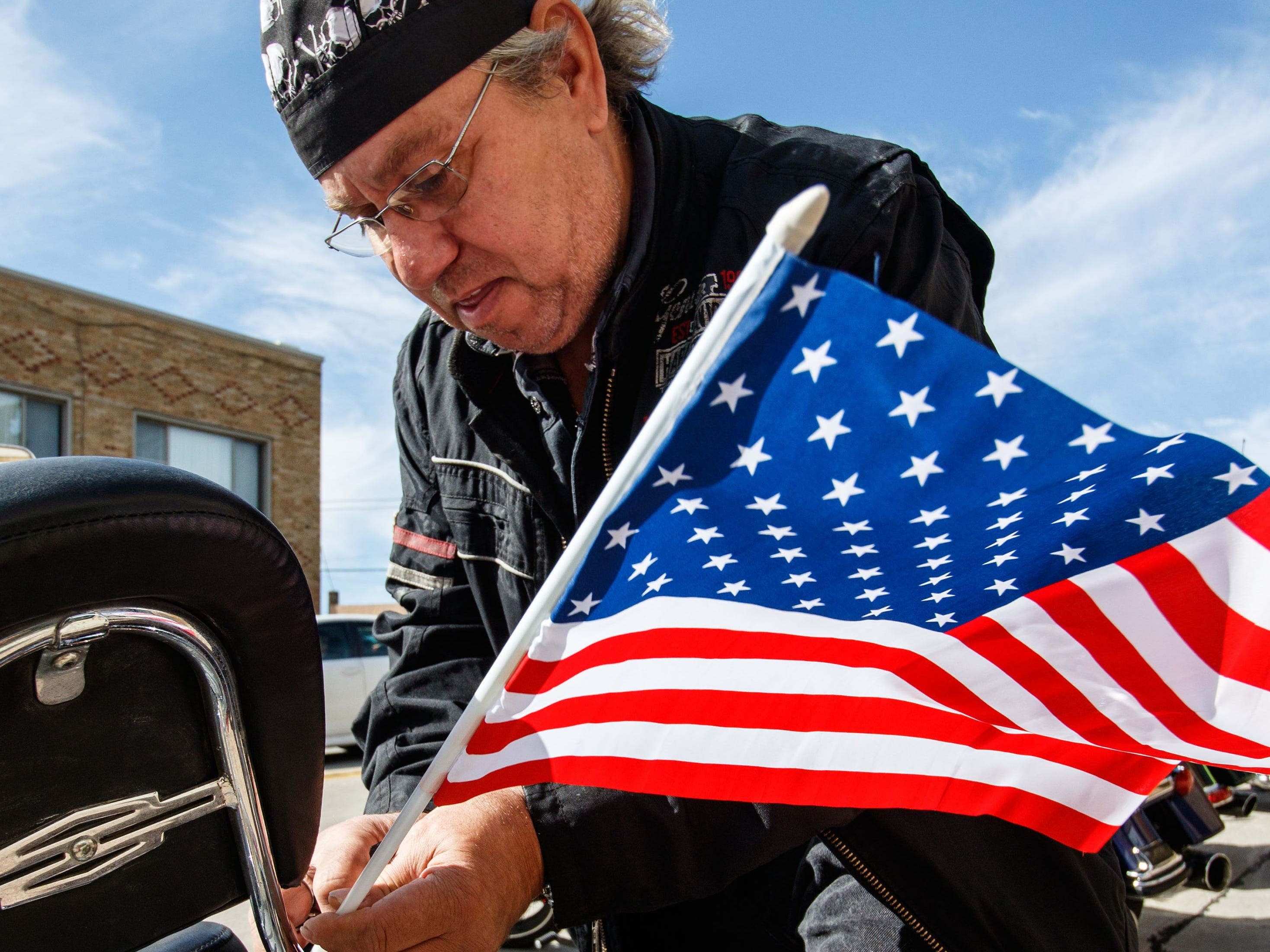 """Karl Emshoff of Wauwatosa attaches a flag to his motorcycle prior to the Angels of the Road """"Ride for Veterans"""" inaugural benefit ride hosted by the Henrizi-Schneider American Legion Post 382 in Menomonee Falls on Sunday, Sept. 9, 2018. Proceeds from the ride will benefit the Milwaukee Homeless Veterans Initiative."""