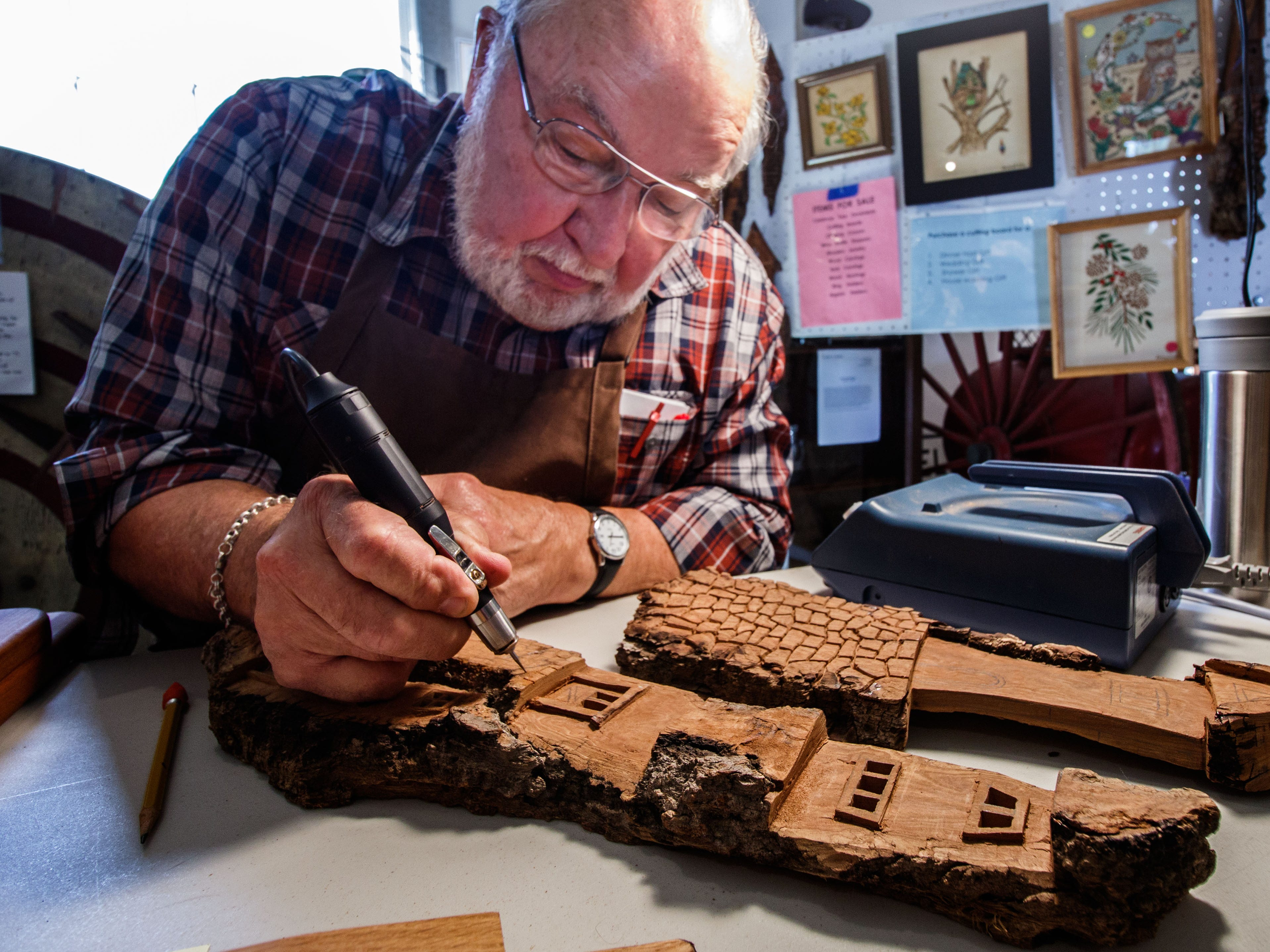 Wood carver Dick Minch of Waukesha works on a whimsical bark carving during Harvest Fest at the Clark House Museum in Pewaukee on Sunday, Sept. 9, 2018. The annual event features hands-on activities and demonstrations of blacksmith, carving, butter churning, corn shelling, square dancing and more.
