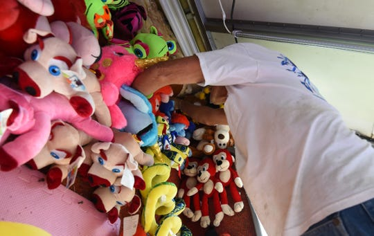 A  worker hangs up stuffed animals at his carnival booth Monday at the Baxter County Fairgrounds.