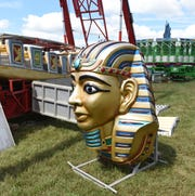 Parts of the Pharaoh's Fury ride sit on the ground while it's being assembled Monday afternoon at the Baxter County Fairgrounds.