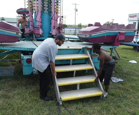 Two workers attach a set of steps to a ride Monday at the Baxter County Fairgrounds.
