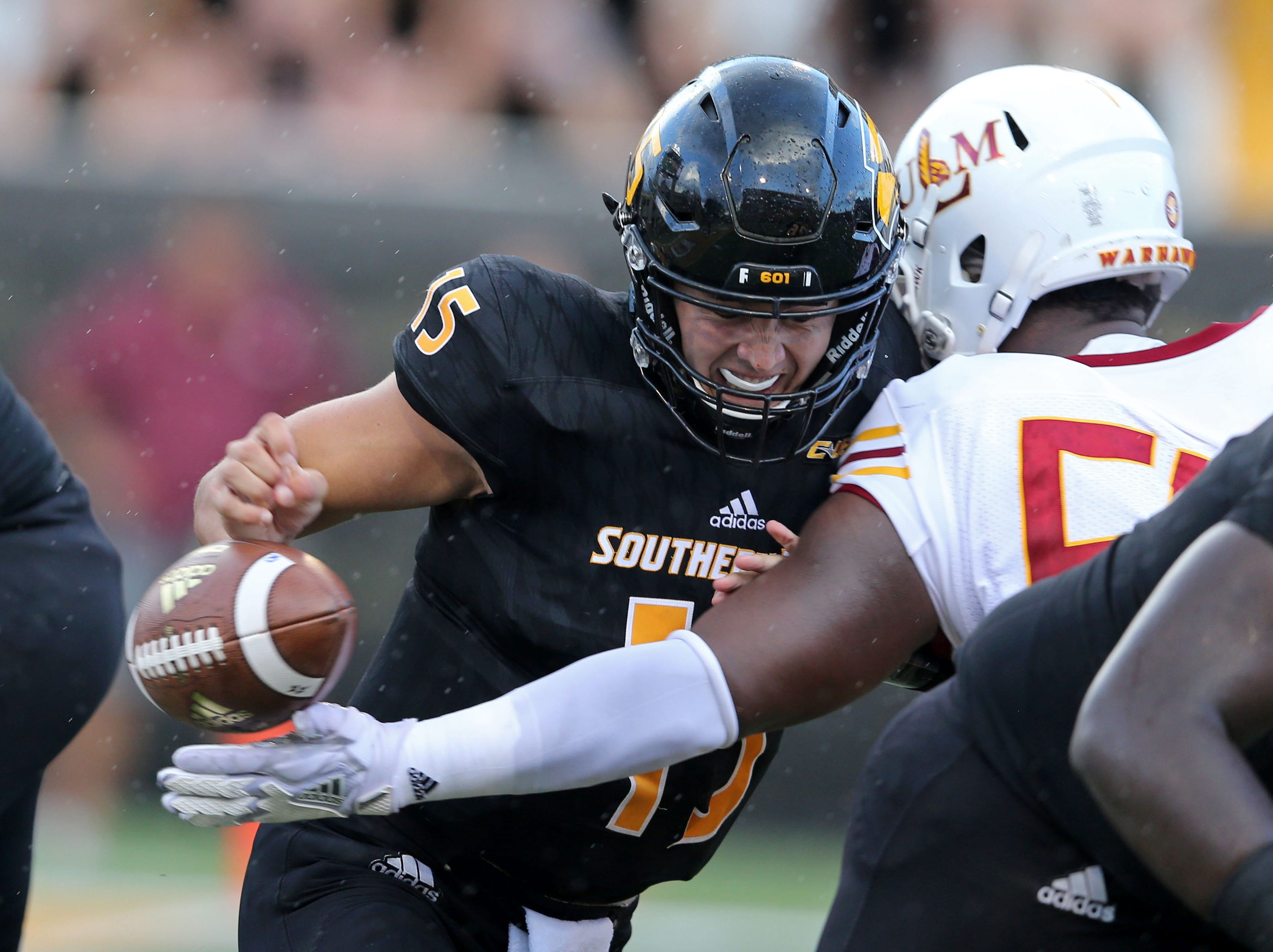 Southern Miss Golden Eagles quarterback Jack Abraham (15) fumbles after being hit by Louisiana Monroe Warhawks defensive lineman Donald Louis Jr. (58), right, at M. M. Roberts Stadium. Louisiana Monroe recovered the ball in the end zone for a touchdown.