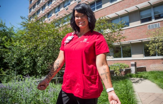 Rebecca Maines with IU Health Ball Memorial Hospital shows her tattoos out in the open after the hospital loosened restrictions requiring tattoos be covered.