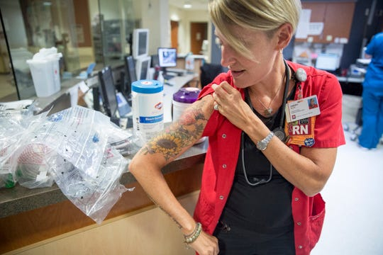 Christi Wohlt, an RN with IU Health Ball Memorial Hospital, shows off her tattoos out in the open after the hospital loosened restrictions requiring tattoos be covered. Prior to the restrictions being lifted employees had to wear long sleeves to cover them.