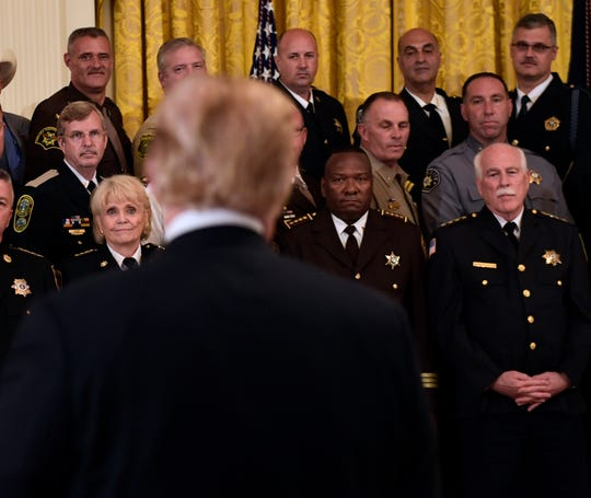 Dickson County Sheriff Jeff Bledsoe, top, right, listens as President Donald Trump talks during an event at the White House in Washington on Sept. 5.