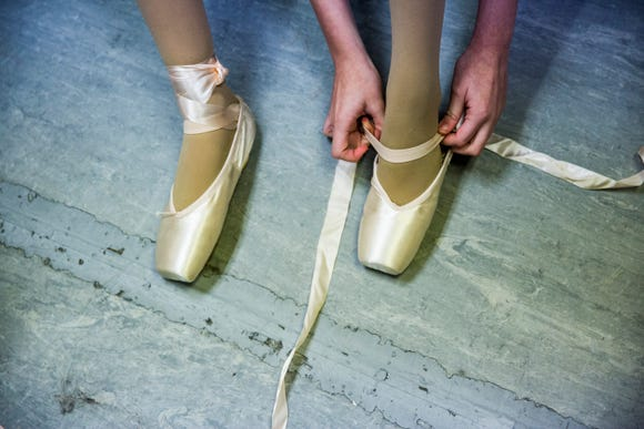 Dancers put on their shoes before a pointe ballet class at Bonita Academy of Dance on Monday, Sept. 10, 2018.