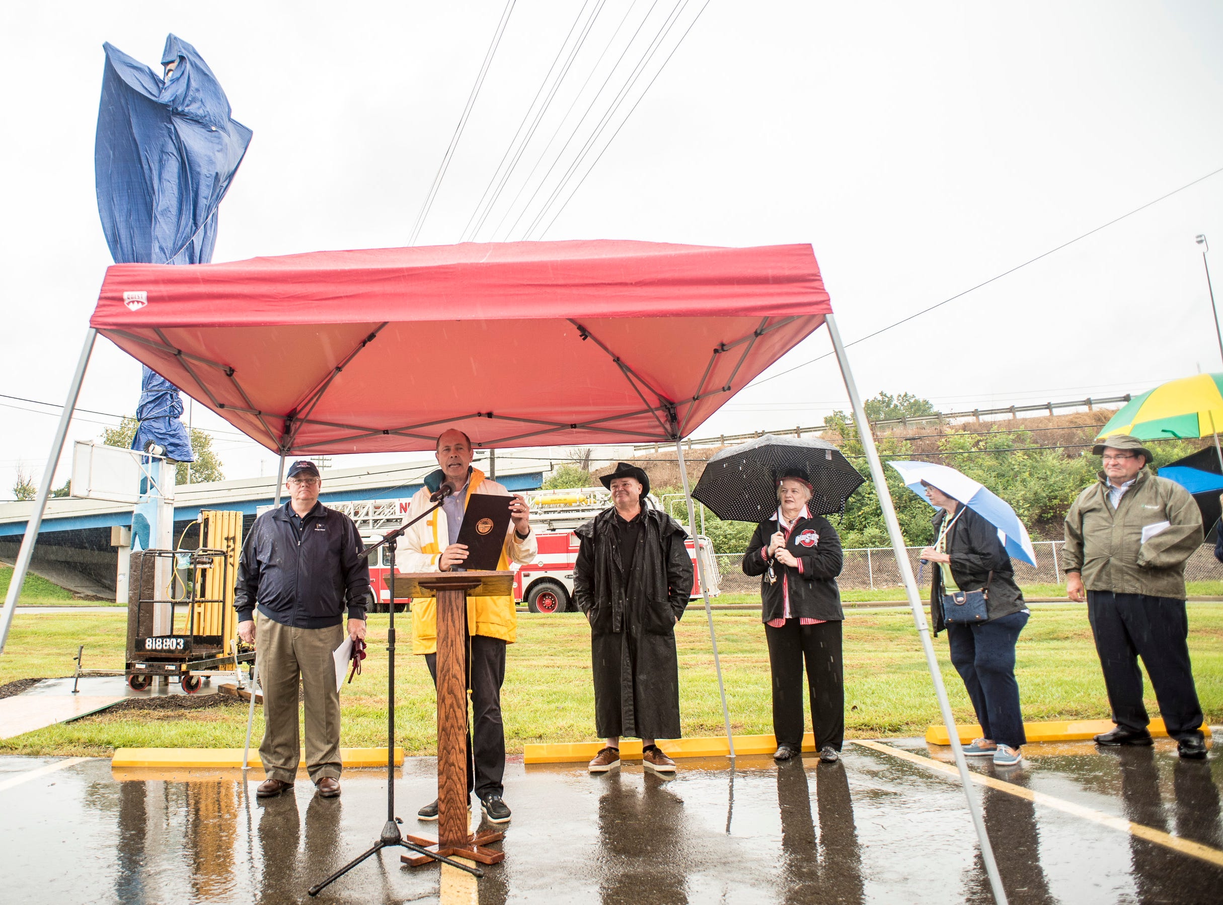 State senator Jay Hottinger reads a proclamation during a ceremony held Saturday to unveil the newly restored totem pole placed near Truck One in Newark, Ohio.