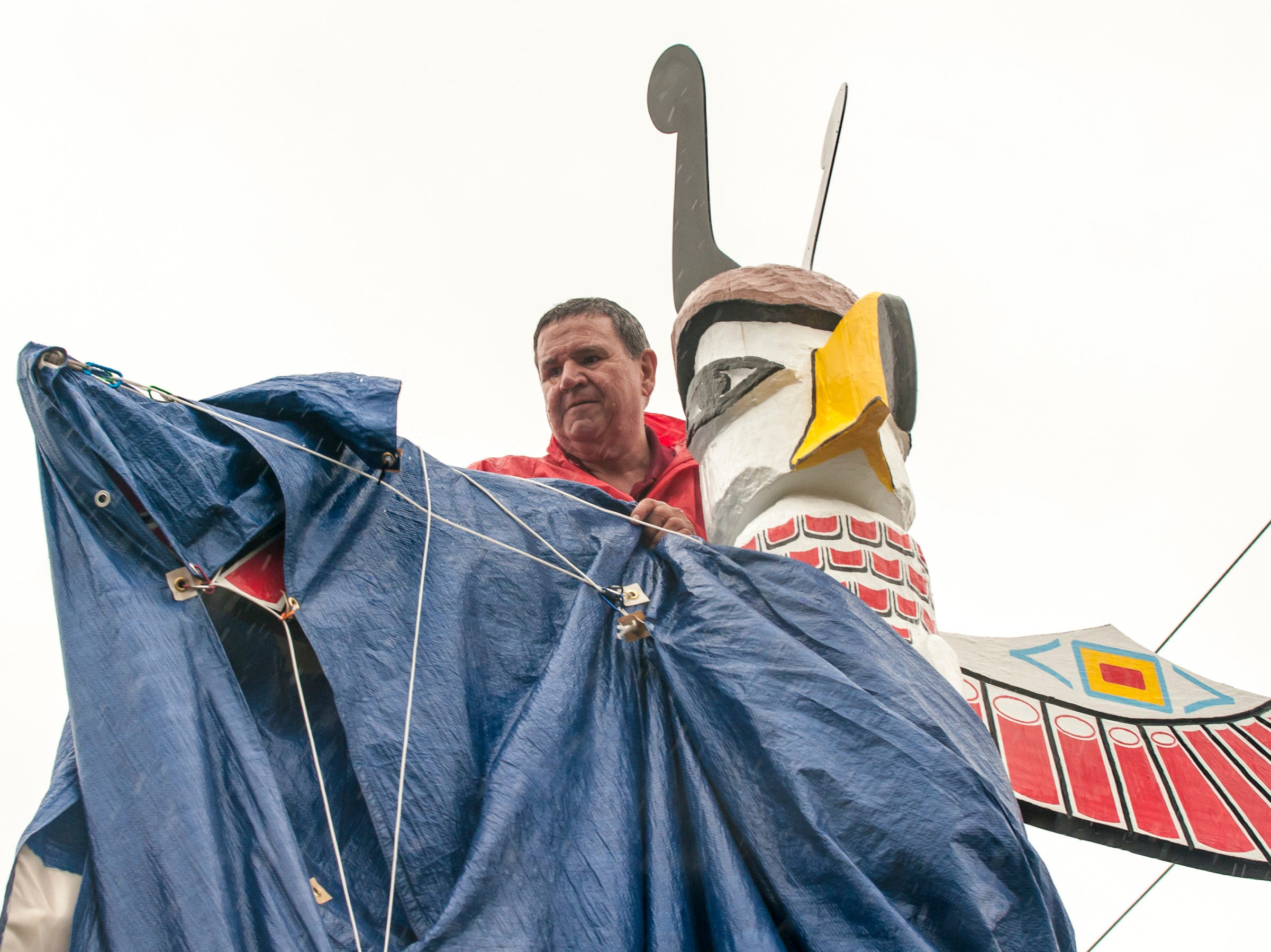 Fred Nickerson removes the tarp during a ceremony held Saturday to unveil the newly restored totem pole placed near Truck One in Newark, Ohio.