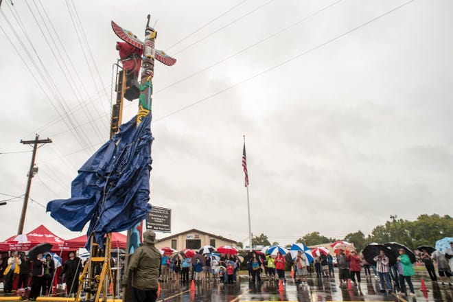 Dave Fryman, on the ground, and Fred Nickerson remove the tarp during a ceremony held Saturday to unveil the newly restored totem pole placed near Truck One in Newark, Ohio.