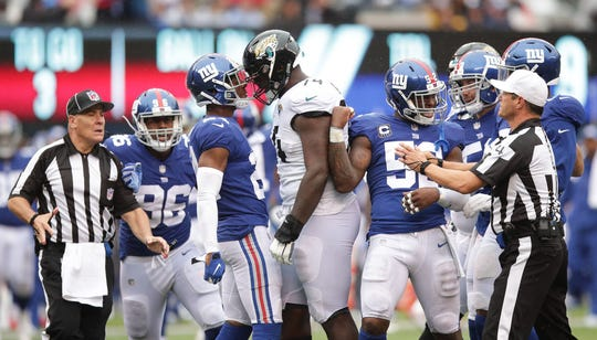 Sep 9, 2018; East Rutherford, NJ, USA; New York Giants cornerback Eli Apple (24) has words with Jacksonville Jaguars offensive tackle Cam Robinson (74) as linebacker Alec Ogletree (52) talks with referee Craig Wrolstad (4) during the second half at MetLife Stadium.