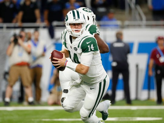 New York Jets quarterback Sam Darnold rolls out before throwing an interception for a touchdown to Detroit Lions cornerback Quandre Diggs (28) in the first quarter of an NFL football game in Detroit, Monday, Sept. 10, 2018. (AP Photo/Rick Osentoski)
