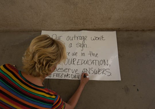 Rio Grande Preparatory Institute student Hazel Bucholz, 20, finishes writing a sign Monday, Sept. 10, 2018 as she and a group of students protest the removal of Kathryn Davis as principal of the school.